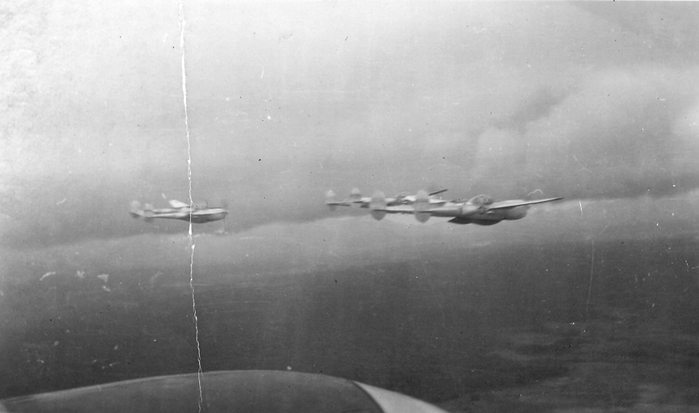 Four P-38 Lightnings from the 449th Fighter Squadron fly in a loose fingertip formation over China in World War II.